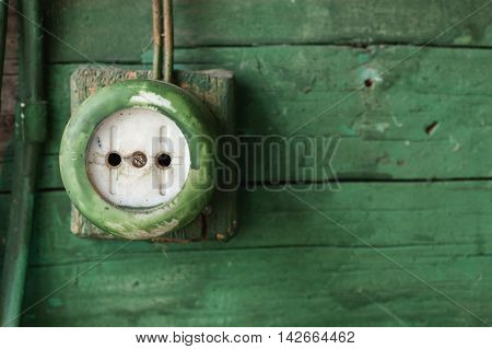 Old Electric Outlet On Green Wooden Wall