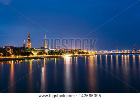 Cityscape At Evening Of Riga, Latvia. Night View With Blue Sky. Copyspace. Nobody. Urban View. Night View Of Cathedral, St. Peter's Church, Bridge And TV Tower