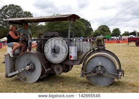 POTTEN END, UK - JULY 27: A large vintage road roller gives a display to the public around the main display arena at the Dacorum Steam fair on July 27, 2014 in Potten End