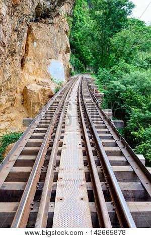 The Death Railway bridge along the cliff and tree located at Kanchanaburi Thailand.