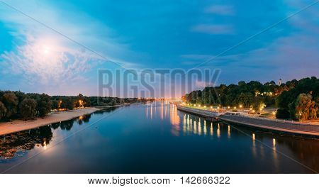 The Scenic Summer Evening View Of Sozh River In Moonlight At Full Moon, Illuminated Embankment And Greenwood Park, Cathedral Of St. Peter And Paul In Gomel, Homiel, Belarus. Blue Sky Background.