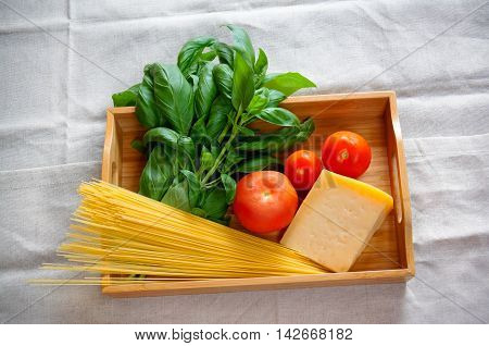 Green basil chunk of parmesan cheese raw cappellini and tomatoes on wooden tray