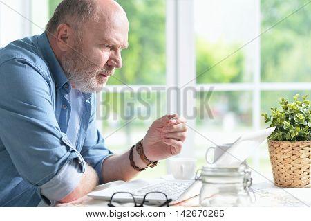 Portrait of a senior man using laptop