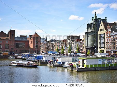 Cityscape of Amsterdam, the Netherlands, with tour boats and church tower.
