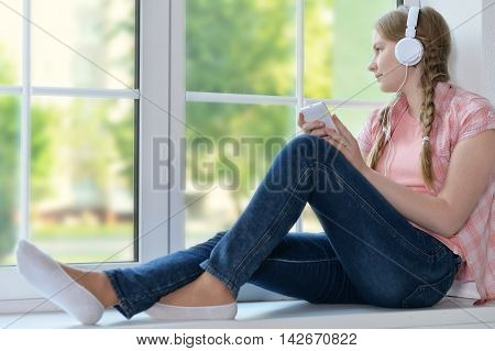 Happy young girl in headphones with smartphone  at home