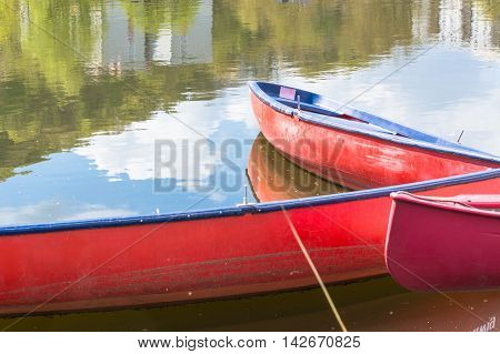 Three blank red canoes lie in the river secured to a jetty on the shore.