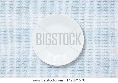 Closeup white ceramic dish on blue fabric mat at the center on dining table in top view with copy space