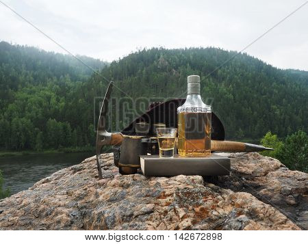 Bottle with alcohol and tourist equipment on the background of forest and river.
