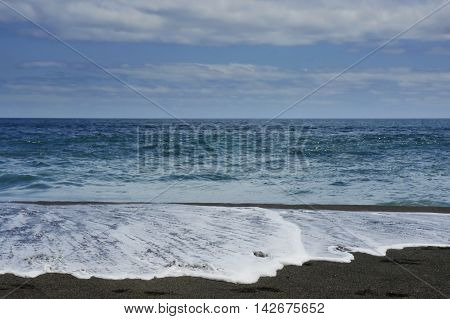 marine landscape Vila Franca atlantic ocean beach in Sao Miguel Azores island of Portugal in summer with vibrant blue sea and waves leaving sand shore foam in travel destination and tourism concept