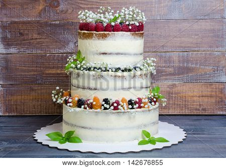 three layered wedding cake with berries and basil leaves