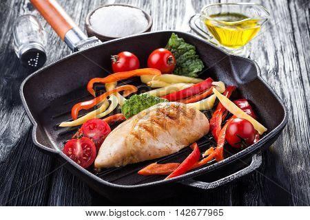 Tasty Grilled chicken fillet and bell pepper on a pap on the black wooden table. Close up