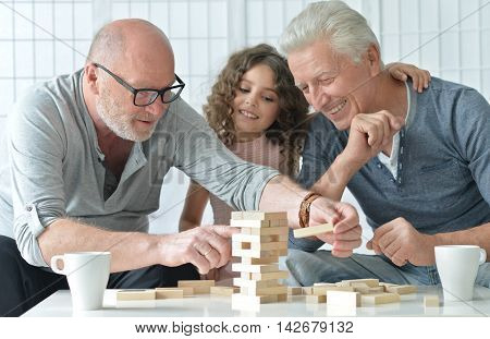 senior men and granddaughter having fun and playing board game at home