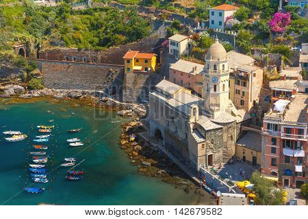 Aerial view with colorful fishing boats and Santa Margherita di Antiochia Church in Vernazza harbour in Five lands, Cinque Terre National Park, Liguria, Italy.