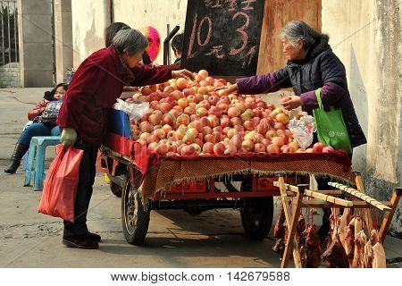 Pengzhou China - January 23 2014: Two Chinese woman buying fresh apples from a street vendor