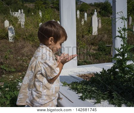 Child visiting grave in cemetery