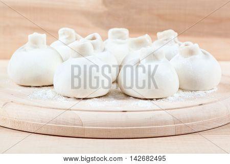 Manti dumplings on the a wooden board.
