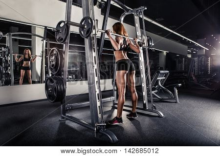 Young sexy girl in the gym doing squat