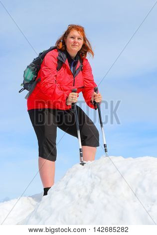 Overweight hiker woman on the top of snowy peak. Active people enjoying outdoor sports in mountain landscape. Healthy lifestyle and slimming concept.