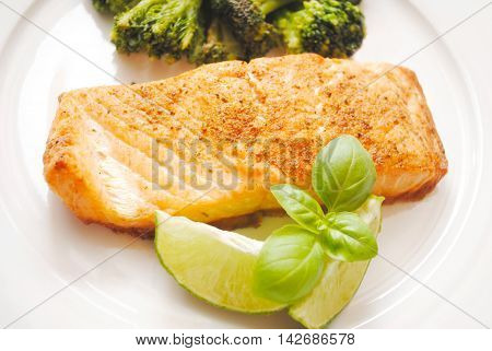 Gourmet Baked Salmon Served with Fresh Basil and Lime Wedges
