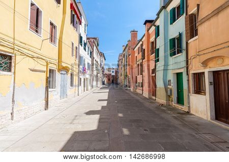 Street feature with multicolored houses in Chioggia the little Venice on a summer day