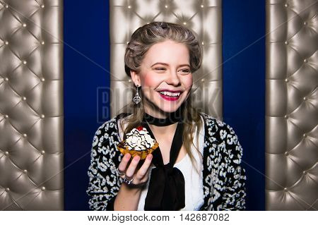 Blonde fashion girl eats cake and laughs Modern interpretation of Marie Antoinette