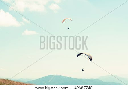 Two Paragliders In Sky With Hills In Background