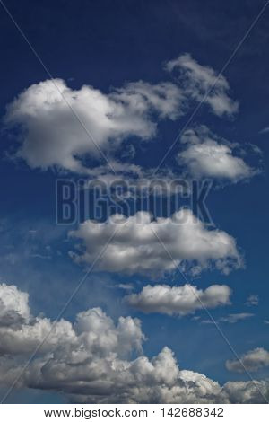 Blue sky with a white cumulus clouds.