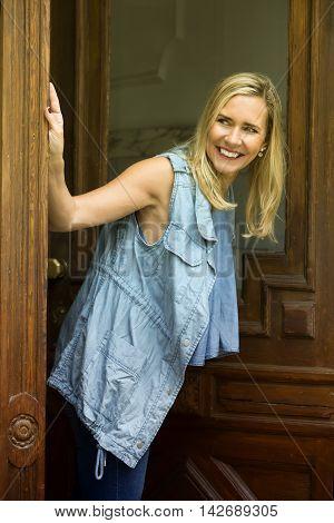 blond woman standing in doorway and looking around