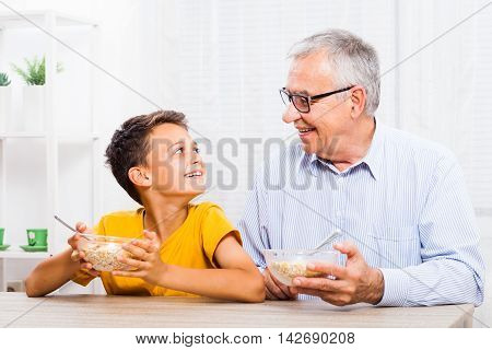 Grandfather and grandson are eating oatmeal at home. Healthy lifestyle.