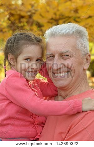 Happy elderly man with granddaughter in autumn park