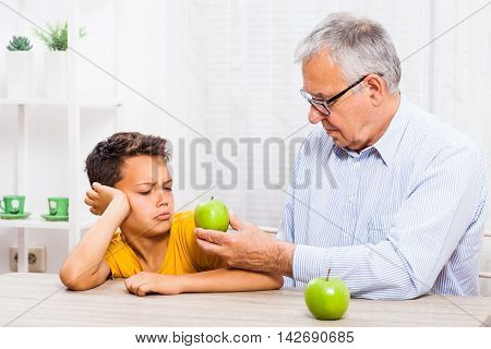 Grandfather is giving apple to his grandson but he refuses to eat it.