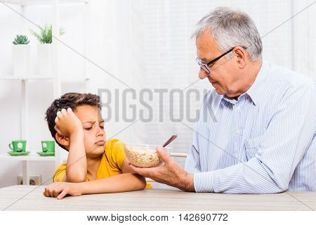 Grandfather is giving oatmeal to his grandson but he refuses to eat it.