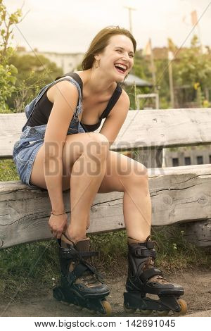 young brunette woman putting on her rollerblades and smiles
