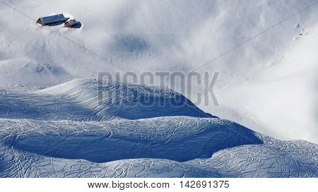 Hills covered by powder snow. Ski and snowboard tracks. Winter scene in the Stoos ski area Swiss Alps.