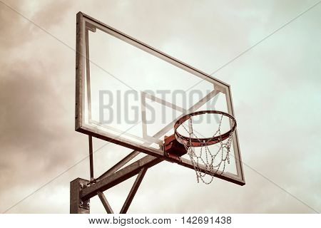 Basketball hoop against a dramatic cloud-filled sky