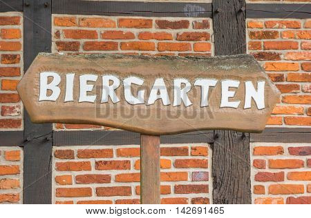 Beer garden sign in front of a traditional german half-timbered wall