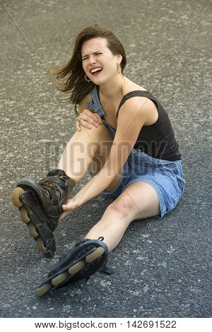 young woman with rollerblades sitting on pavement with pain after an accident