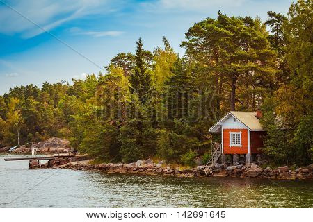 Red Finnish Wooden Sauna Log Cabin On Island In Autumn