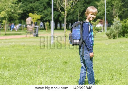 Child with a backpack go to school. Outdoor. Back view. Education, back to school, people concept.