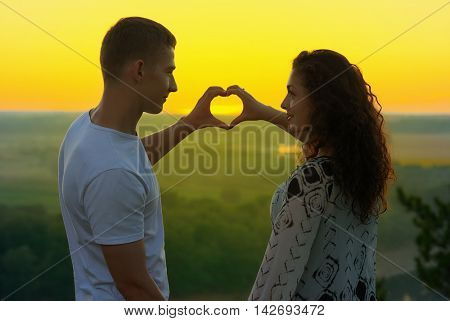 romantic couple at sunset show a heart shape from hands, beautiful landscape and bright yellow sky, love tenderness concept, young adult people