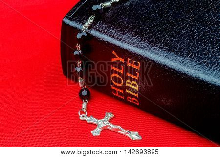 Bible and crucifix with rosary beads on a red canvas surface