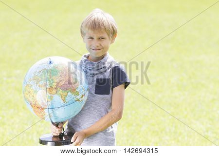 Smiling boy with a globe outside. Education, Back to school concept