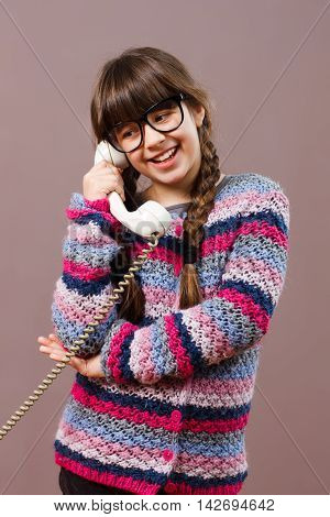Beautiful little nerdy girl is talking with someone on the phone.
