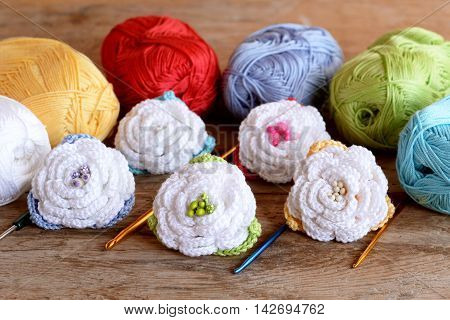 Crochet flowers kit, cotton yarn skeins, hooks of different size on old wooden background. White crocheted roses with colorful leaves. Crafts idea for kids or beginners