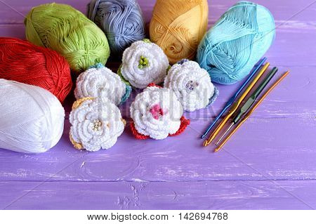 Crochet flowers set, cotton yarn skeins, hooks of different size on purple wooden background. Colorful crocheted roses. Handicraft idea for kids or beginners