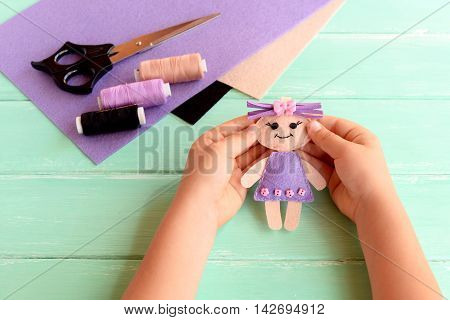Child holds a small doll in his hands. Doll is sewn from felt. Scissors, thread and felt set on a wooden table. Cute fabric art and craft idea for kids