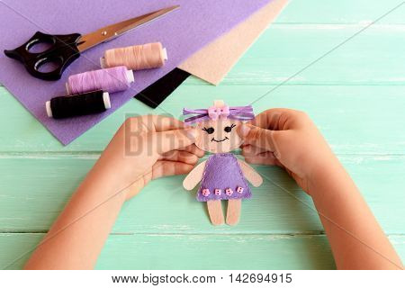 Child holds a felt doll in his hands and shows it. Scissors, thread, felt sheets on a table. Cute stuffed toy is made manually. Easy sewing project for kids