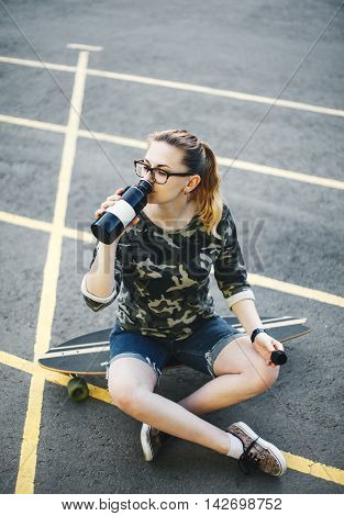 Young girl sitting on a longboard and drinks water from a metal bottle