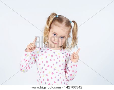 Little Girl Wearing  Pointing By Forefinger To Somewhere Up