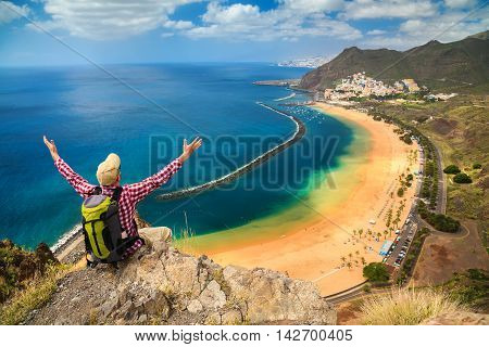 man with opened arms sitting on the edge of a cliff enjoying amazing sea view of the beach near Santa Cruz de Tenerife - Playa de Las Teresitas Canary Islands Spain